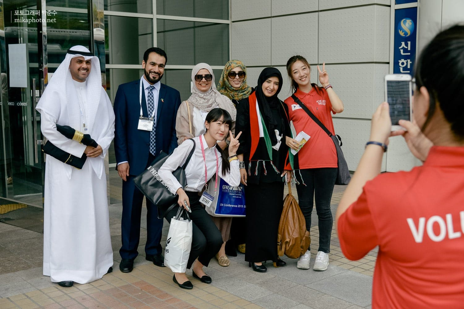 Delegate from Kuwait takes a picture with volunteers.